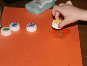 kids making bottlecap caterpillar craft