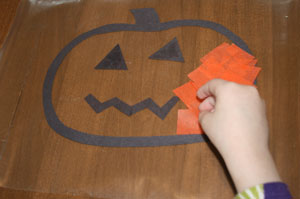 adding tissue paper to pumpkin craft